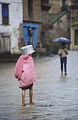 Young girl walking under the rain, Newar ethnic group, Bhaktapur, Nepal