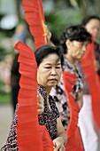 Morning exercises with hand-held fan, near Hoan Kiem lake, Hanoi, Vietnam