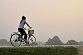 Woman cycling on a dike, Kenh Ga, Ninh Binh province, Vietnam