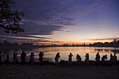Korean tourists taking photographs of the sunset in front of the royal pool of Srah Srang, Angkor, Siem Reap, Cambodia