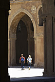 Touristic couple walking at Mosque of Ahamad ibn Tulun, Cairo. Egypt