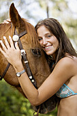 Adult, Adults, Affection, Animal, Animals, Bikini, Bikinis, Blue eyed, Blue eyes, Blue-eyed, Brown hair, Brown haired, Caress, Caresses, Caressing, Caucasian, Caucasians, Chestnut hair, Color, Colour, Contemporary, Daytime, Equitation, exterior, Facial ex