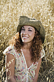 Adult, Adults, Brown hair, Brown haired, Caucasian, Caucasians, Chestnut hair, Color, Colour, Contemporary, Country, Countryside, Daytime, exterior, Facial expression, Facial expressions, Facing camera, Female, Grass, Grasses, grin, grinning, Hat, Hats, H