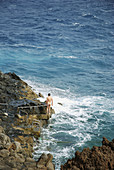 Nudist man on the rocks by the sea, natural pool in Charco del Palo, Lanzarote island, Canary Islands, Spain