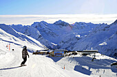 Female snowboarder on slope, ski lodge in background, Davos, Grisons, Switzerland