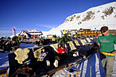 Persons sunbathing near alpine lodge, Davos, Grisons, Switzerland