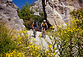 Two people riding mountain bikes between rocks in the sunlight, Lycia, Turkey, Europe