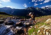 A woman carrying her mountain bike across a mountain stream, Tyrol, Austria, Europe