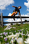 Young man jumping over a fence, Dolomites, South Tyrol, Italy, Europe