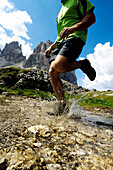 Man running through a mountain stream, Dolomites, South Tyrol, Italy, Europe
