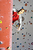 Young man at a climbing wall in a hall, Bad Toelz, Bavaria, Germany, Europe
