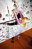 Young woman at a climbing wall in a hall, Bad Toelz, Bavaria, Germany, Europe