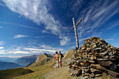 Hikers in the mountains next to a summit cross, South Tyrol, Italy, Europe