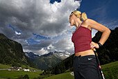 Young woman nordic walking under clouded sky, Tyrol, Austria, Europe