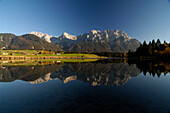 Reflection of mountains on lake Schmalensee under blue sky, Bavaria, Germany, Europe