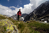 Woman at hike in the mountains in front of white clouds, Hohe Tauern, Austria, Europe