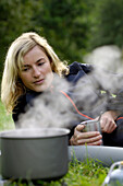 Camping, cooking pot and blonde woman on a meadow, Franconian Switzerland, Bavaria, Germany, Europe