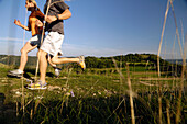 Couple jogging on a meadow, Franconian Switzerland, Bavaria, Germany, Europe