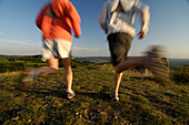 Couple jogging in the light of the evening sun, Franconian Switzerland, Bavaria, Germany, Europe