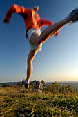 Jogger during a jump in the evening light, Franconian Switzerland, Bavaria, Germany, Europe