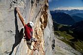 Climber at Schuesselkar rock face in the sunlight, Tyrol, Austria, Europe