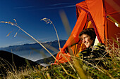 Young woman looking out of a tent in the mountains, Tyrol, Austria, Europe