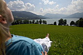 Young woman lying in the grass, near lake Tegernsee, Upper Bavaria, Bavaria, Germany