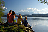 Family sitting on the shore of lake Staffelsee, near Murnau, Upper Bavaria, Bavaria, Germany
