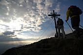 Two people at the summit cross, ascent to Klammspitze, Ammergau Alps, Ammergau, near Oberammergau, Bavaria, Germany