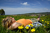 Woman lying in a meadow, hiking tour near Tabarz, near Eisenach, Thuringia, Germany
