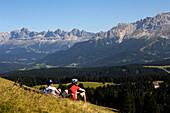Couple having a rest, mountainbike tour, MTB, Rosengarten Mountain Range, Dolomiten, South Tyrol, Italy, Europe