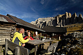 Couple having a rest at an alpine hut, near Wolkenstein, view of Sella mountains, Gardena Valley, Dolomites, South Tyrol, Italy, Europe