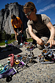 Two women sorting their climbing equipment, quickdraws, cams and friends, Yosemite National Park, California, USA