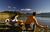 Family hiking at Lake Tegernsee, throwing stones into the water, Upper Bavaria, Bavaria, Germany, Europe