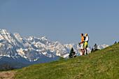 Couple on a mountain pasture admiring the view, Wallgau, Karwendel, Upper Bavaria, Bavaria, Germany, Europe
