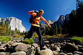 Woman wearing rucksack jumping over stones at brookside, Yosemite National Park, California, North America, America