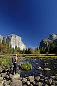 Female hiker enjoying view over Merced River, Yosemite National Park, California, USA