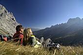 Couple resting on mountain meadow, Val di Fassa, Dolomites, Trentino-Alto Adige/Südtirol, Italy
