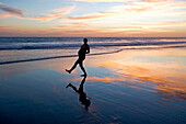 Pregnant woman walking on the beach and holding her stomach, sunset, Conejo beach, Baja California Sur, Mexico