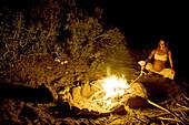 Pregnant woman standing near a campfire, Conejo, Baja California Sur, Mexico