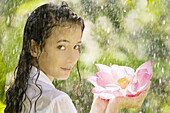 17-19, Beauty, Body care, Casual, Caucasian, Clothing, Color, Colour, Contemporary, Flower, Fragility, Freshness, Green, Head & shoulders, Head and shoulders, Health, Holding, Looking, Lotus, One person, Outdoors, Over, Pink, Portrait, Rain, Shoulder, Sho
