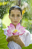 17-19, Beauty, Body care, Casual, Caucasian, Clothing, Color, Colour, Contemporary, Flower, Fragility, Freshness, Green, Head & shoulders, Head and shoulders, Health, Holding, Leaf, Looking at camera, Lotus, One person, Outdoors, Pink, Portrait, Rain, Sho