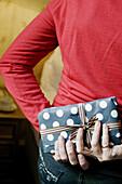 Eine Person, Eingewickelt, Eins, Erwachsene, Erwachsener, Farbe, Frau, Frauen, Geschenk, Geschenke, Geschenkpapier, Halten, Hand, Hände, Innen, Konzept, Konzepte, Mensch, Menschen, Nahaufnahme, Nahaufnahmen, Paket, Rückenansicht, Stehen, Stehend, Überrasc