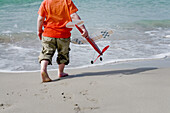 Aeroplane, Aeroplanes, Aircraft, Aircrafts, Airplane, Airplanes, Amusement, back view, Barefeet, Barefoot, beach, beaches, Boy, Boys, Carry, Carrying, Child, childhood, Children, Color, Colour, Contemporary, Daytime, exterior, Foam, Foamy, Froth, Fun, Hol