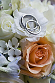 Wedding rings on top of rose flower bouquet