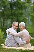Adult, Adults, Affection, Amusement, back view, Bond, Bonding, Bonds, Caucasian, Caucasians, Color, Colour, Contemporary, couple, couples, Daytime, embrace, embracing, exterior, Facing camera, female, Fondness, Fun, Grass, grin, grinning, happiness, happy