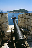 Looking along barrel of cannon toward passing galleon and Lokrum Island, from old city walls, Dubrovnik, Dalmatian Coast, Croatia, Former Yugoslavia
