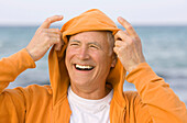 Adult, Adults, beach, beaches, Caucasian, Caucasians, Color, Colour, Contemporary, Daytime, exterior, Exuberance, Exuberant, Gesture, Gestures, Gesturing, Gray-haired, Grey hair, Grey haired, Grey hairs, Grey-haired, grin, grinning, happiness, happy, Head