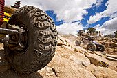 Blick auf einen Rennwagenreifen bei einem Rock Crawling Rennen wo im Hintergrund ein Rennwagen vorbei fährt, Rock Crawling, Moab, Utah, USA