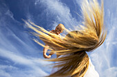 A woman with hair flying holds her 5 month old baby in the air, Nine Palms, Baja California Sur, Mexico